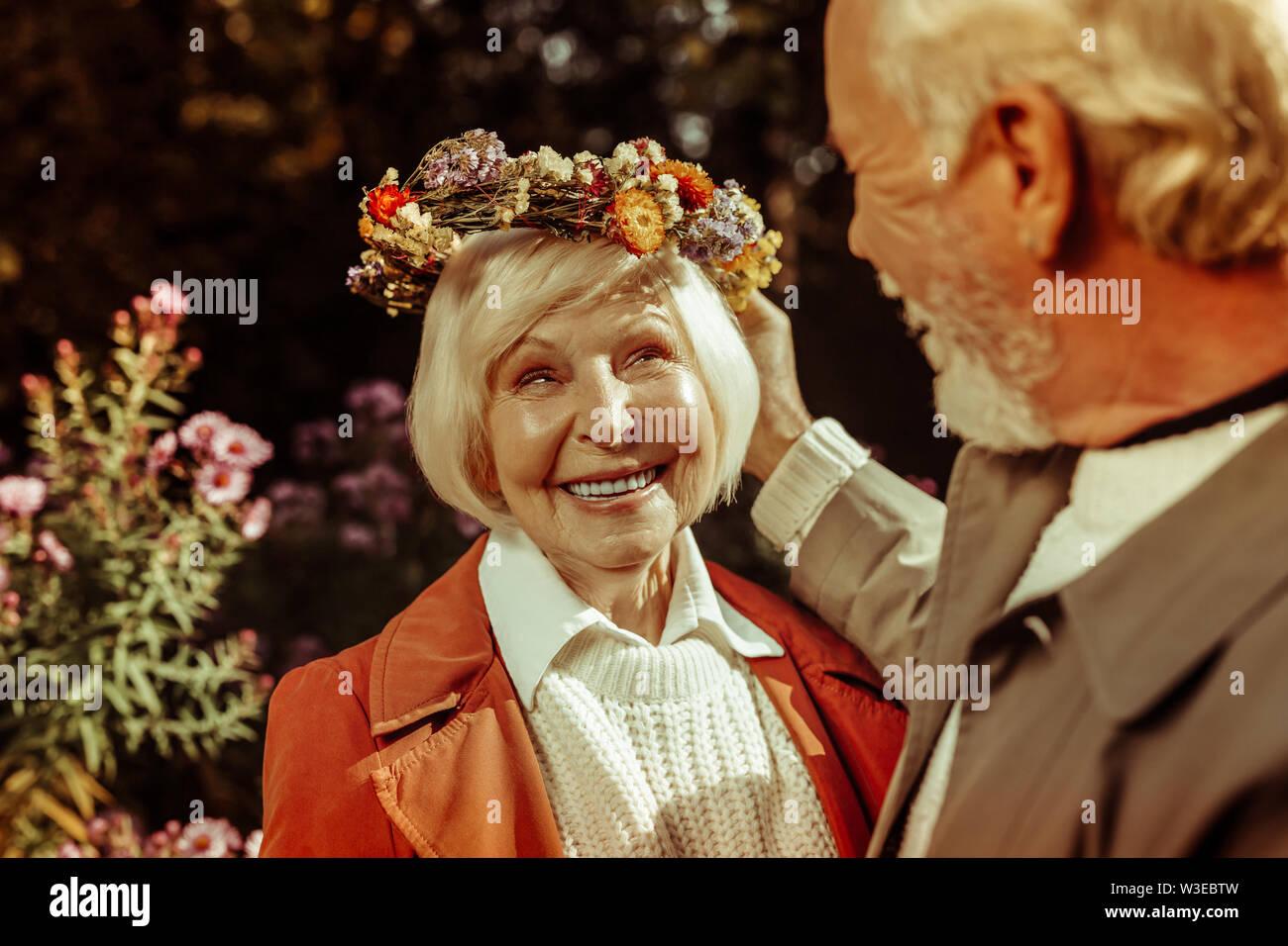 Femme âgée portant couronne de fleurs et souriant à son mari. Photo Stock