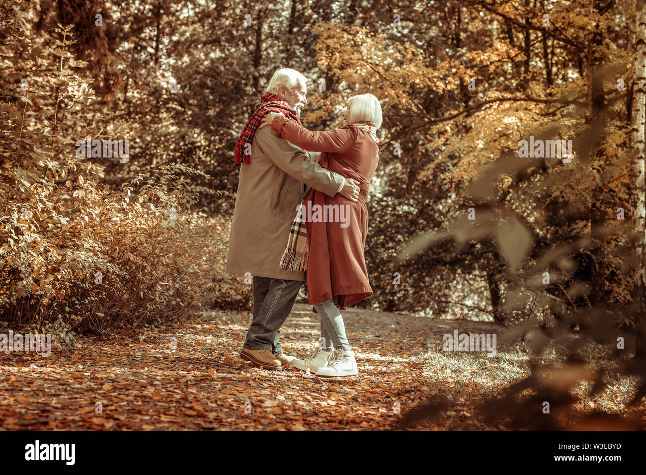Happy senior man hugging son épouse dans un parc. Photo Stock