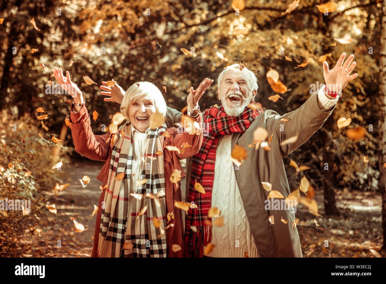 Heureux couple âgé de jeter les feuilles d'automne. Photo Stock