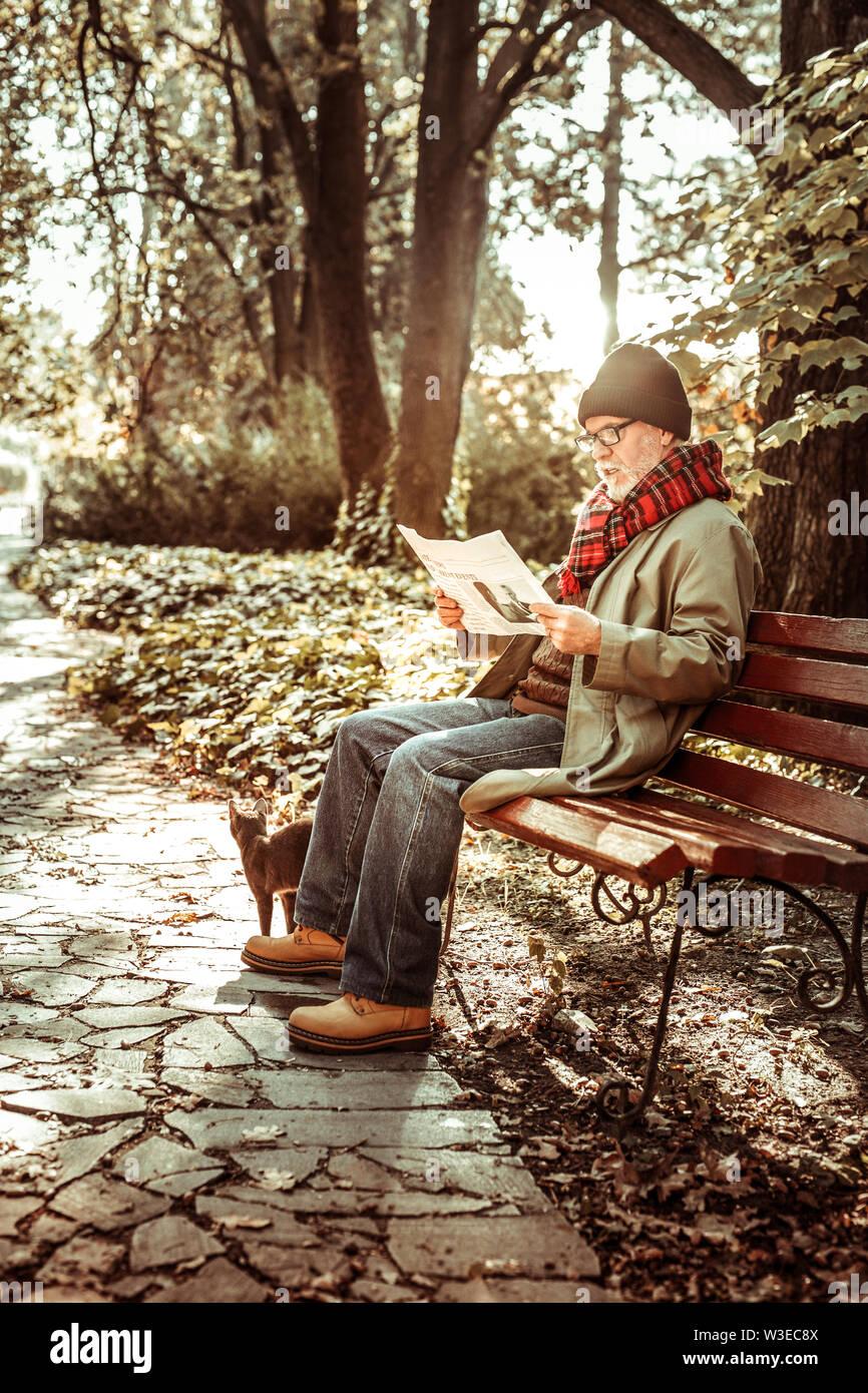 Homme âgé lire son journal dans le parc. Photo Stock