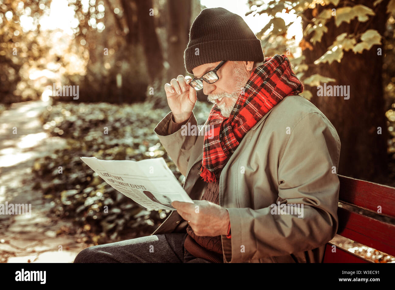 Homme d'âge concentrée la lecture attentive d'un journal. Photo Stock