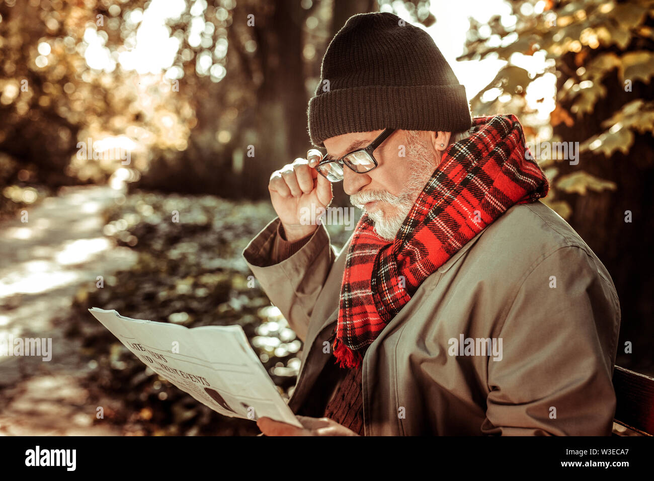 Vieil homme barbu assis sur le banc avec un journal. Photo Stock