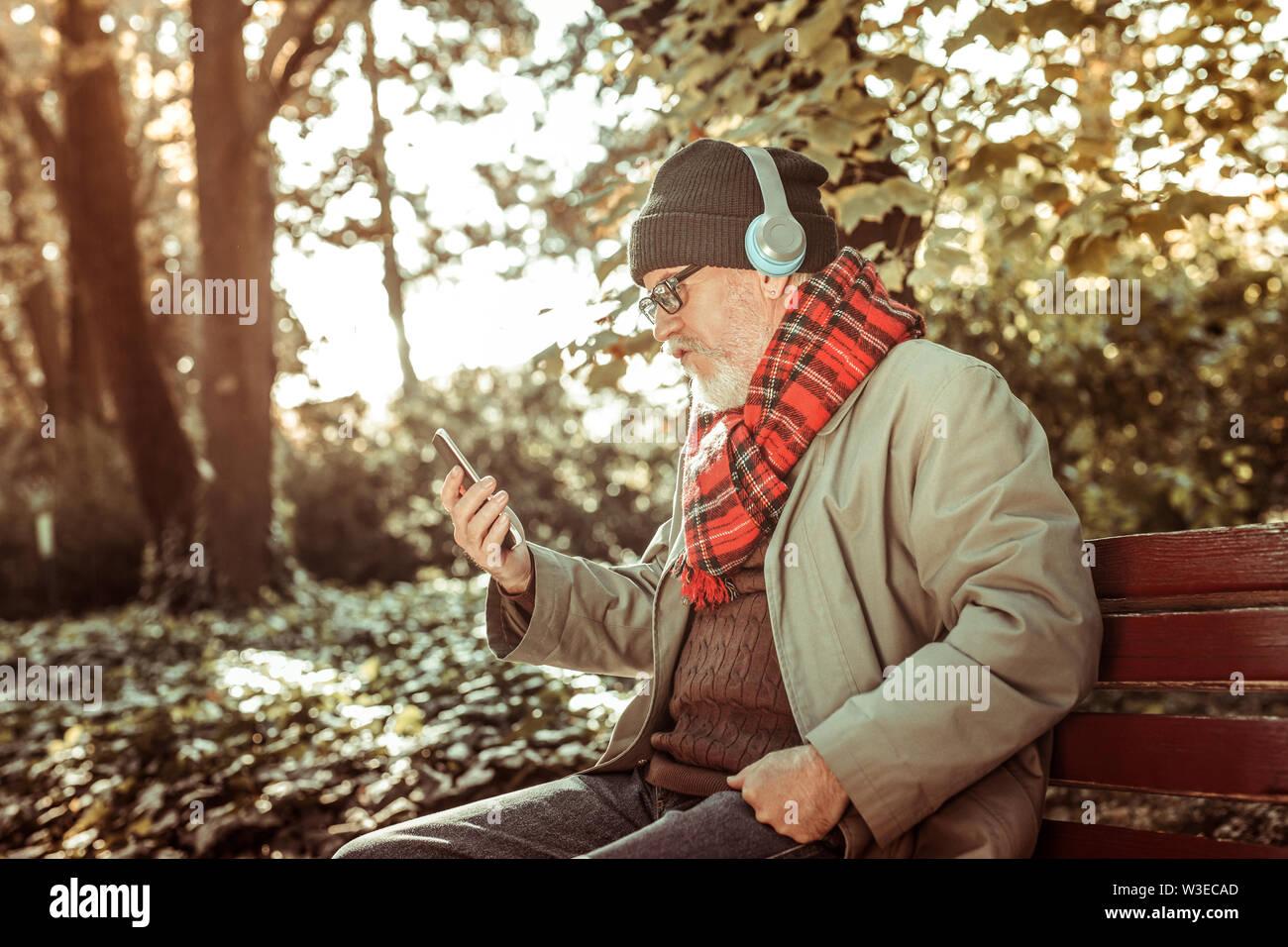 Homme sérieux d'écouter de la musique à partir de son smartphone. Photo Stock