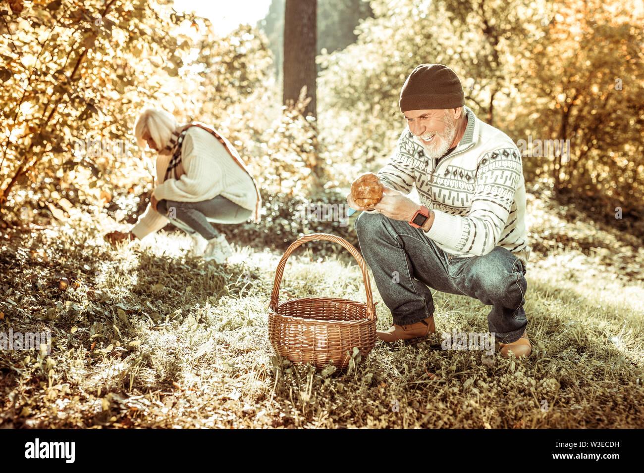 Cheerful senior homme qui les champignons avec sa femme. Photo Stock