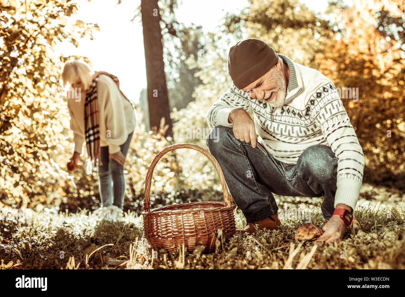 Happy senior couple recueillir des champignons dans la forêt ensemble. Photo Stock