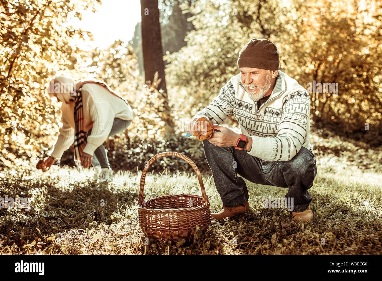 Homme heureux trouver un gros champignon dans la forêt. Photo Stock