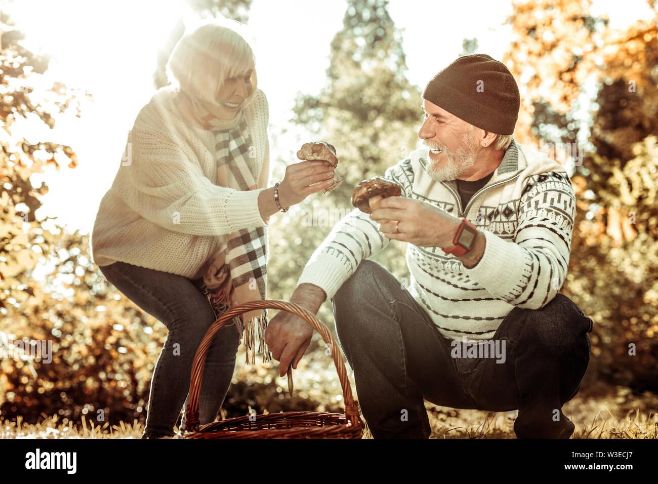 Mari et femme comparant des champignons dans la forêt. Photo Stock