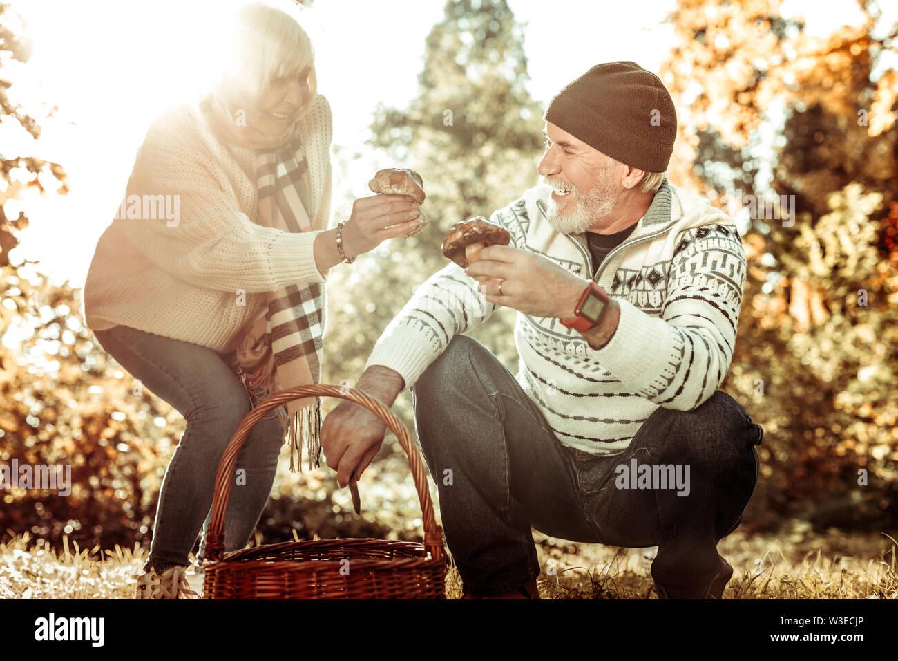 Mari et femme souriante champignons collecte ensemble. Photo Stock