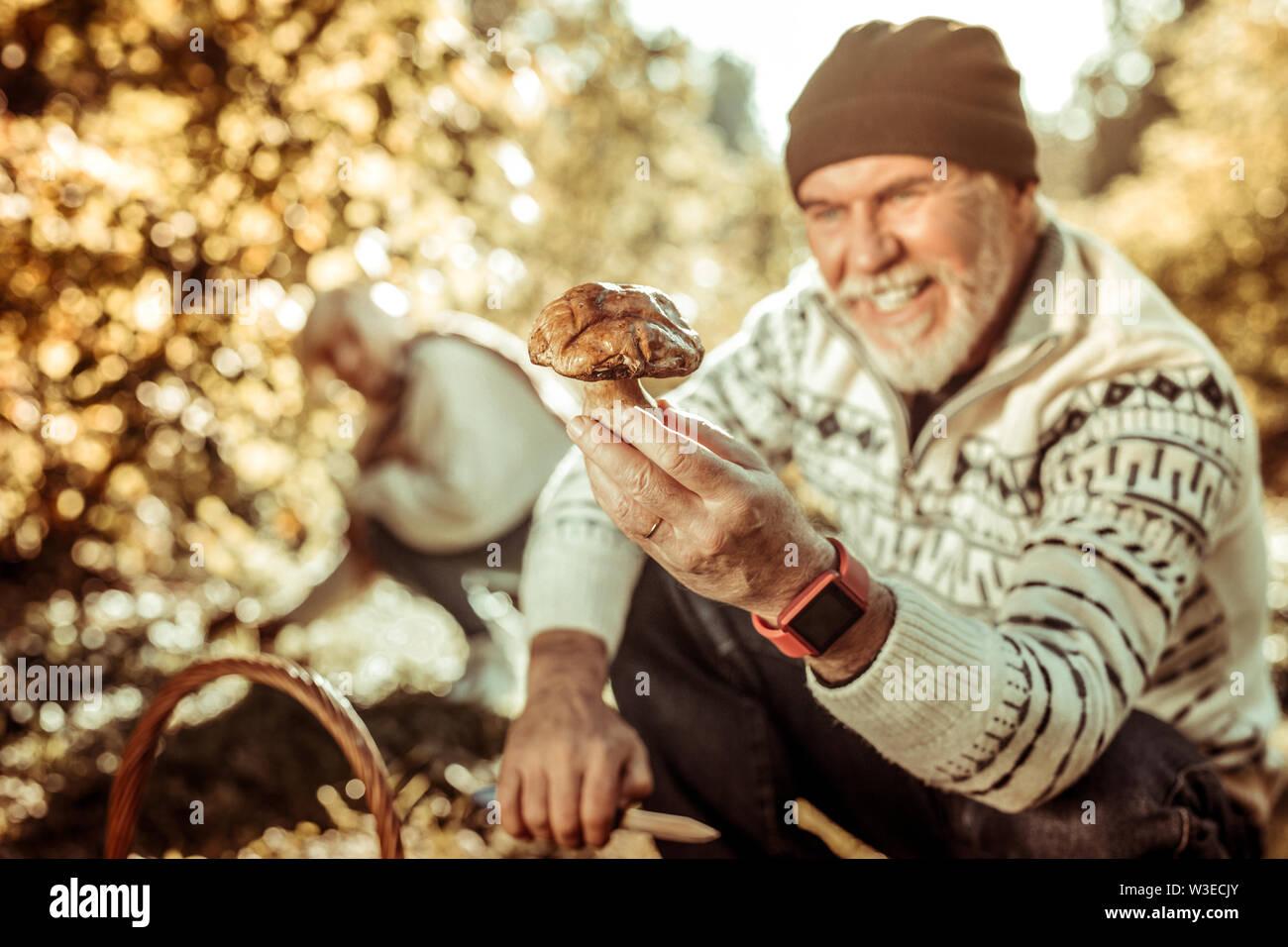 Gros champignon dans une main de l'homme heureux. Photo Stock