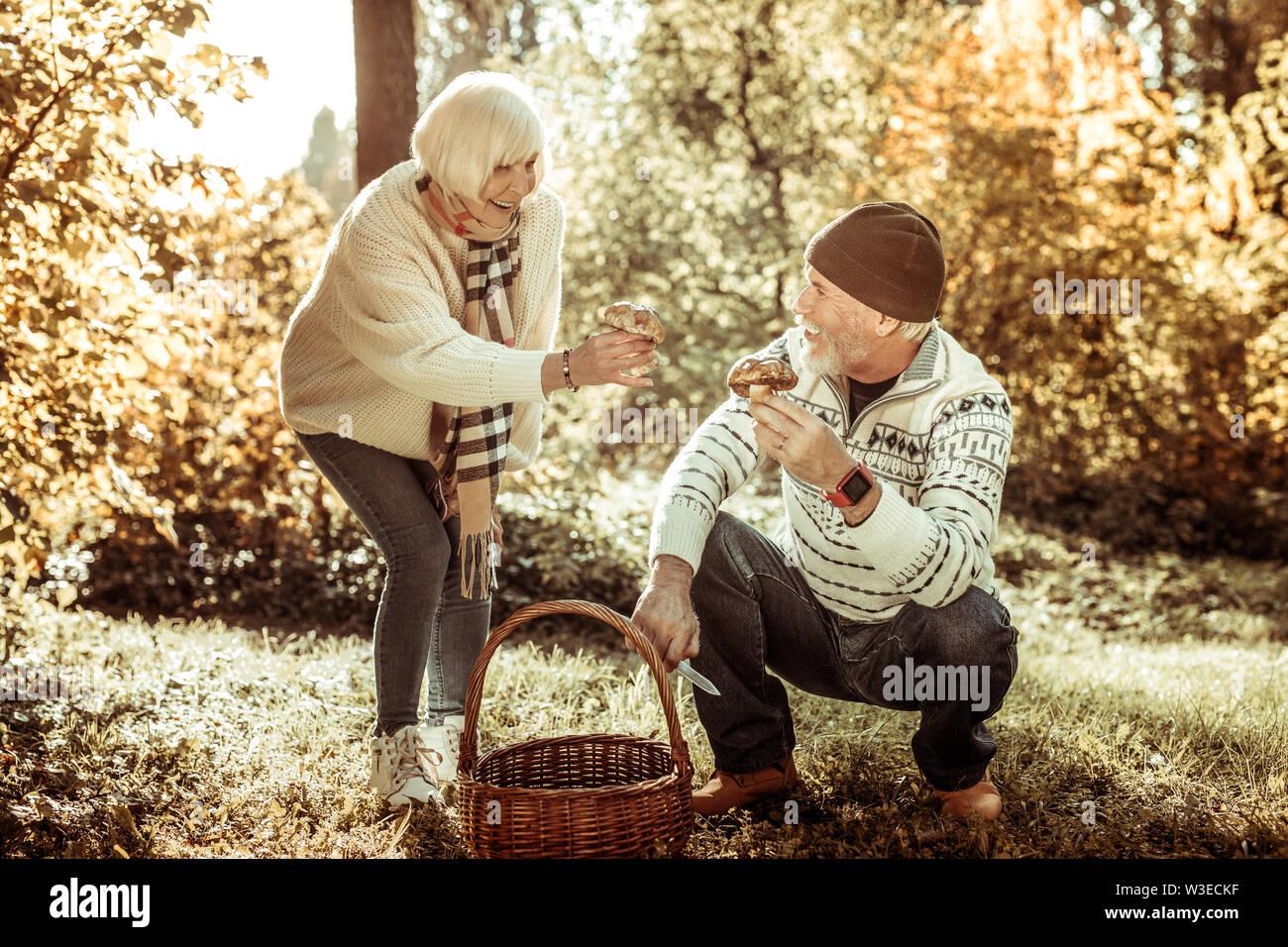 Heureux couple montrant chaque autres champignons qu'ils ont trouvé. Photo Stock