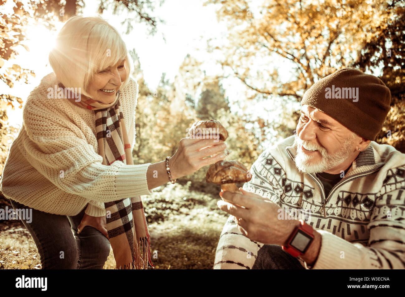 Mari et femme trouver gros champignons dans la forêt. Photo Stock