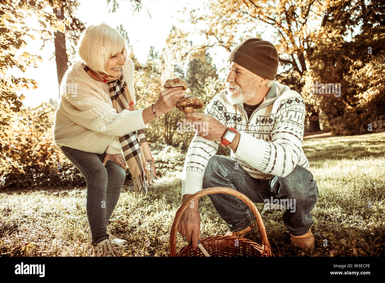 Mari et femme tenant des champignons dans la forêt. Photo Stock