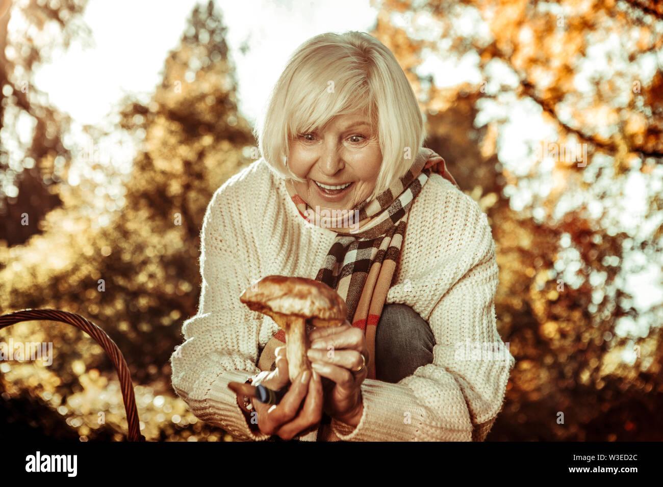 Belle femme âgée a été surpris de trouver un champignon. Photo Stock