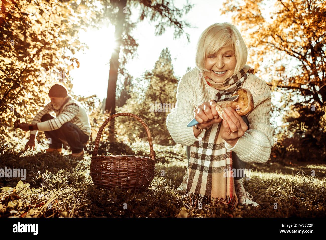 Smiling woman cutting un stipe d'un champignon. Photo Stock