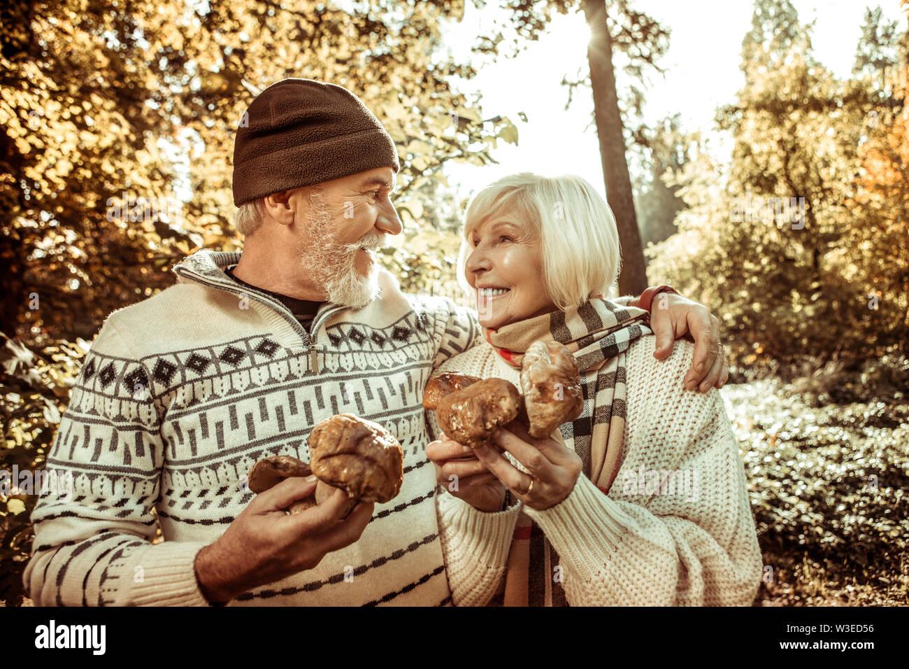 Heureux couple holding big champignons et s'étreindre. Photo Stock