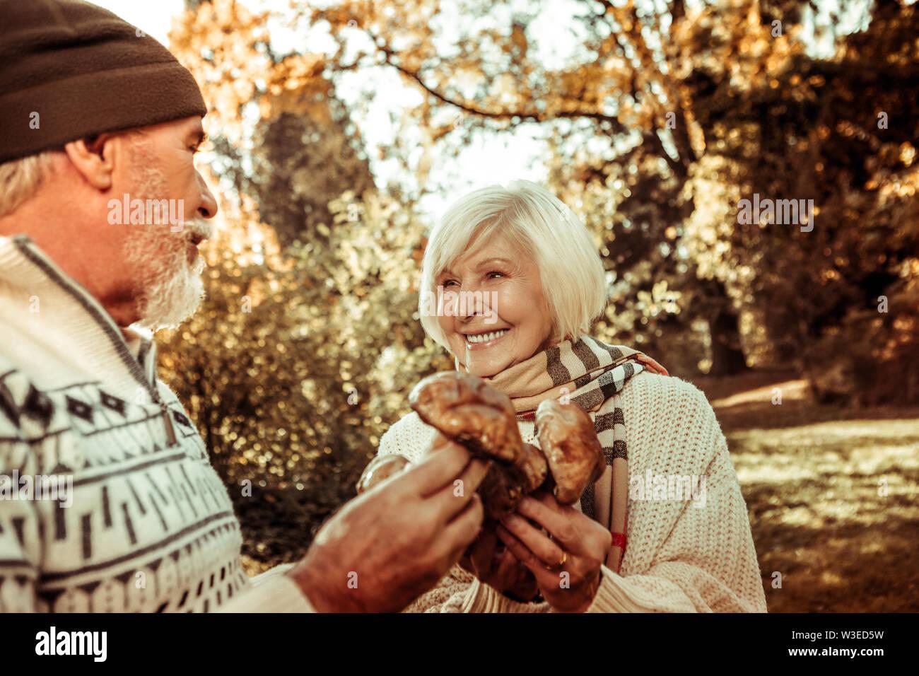 Happy woman holding champignons et regardant son mari. Photo Stock