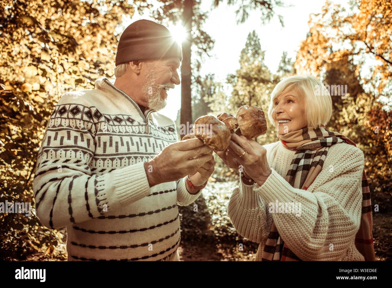 Mari et femme tenant les champignons et à la recherche à l'autre. Photo Stock