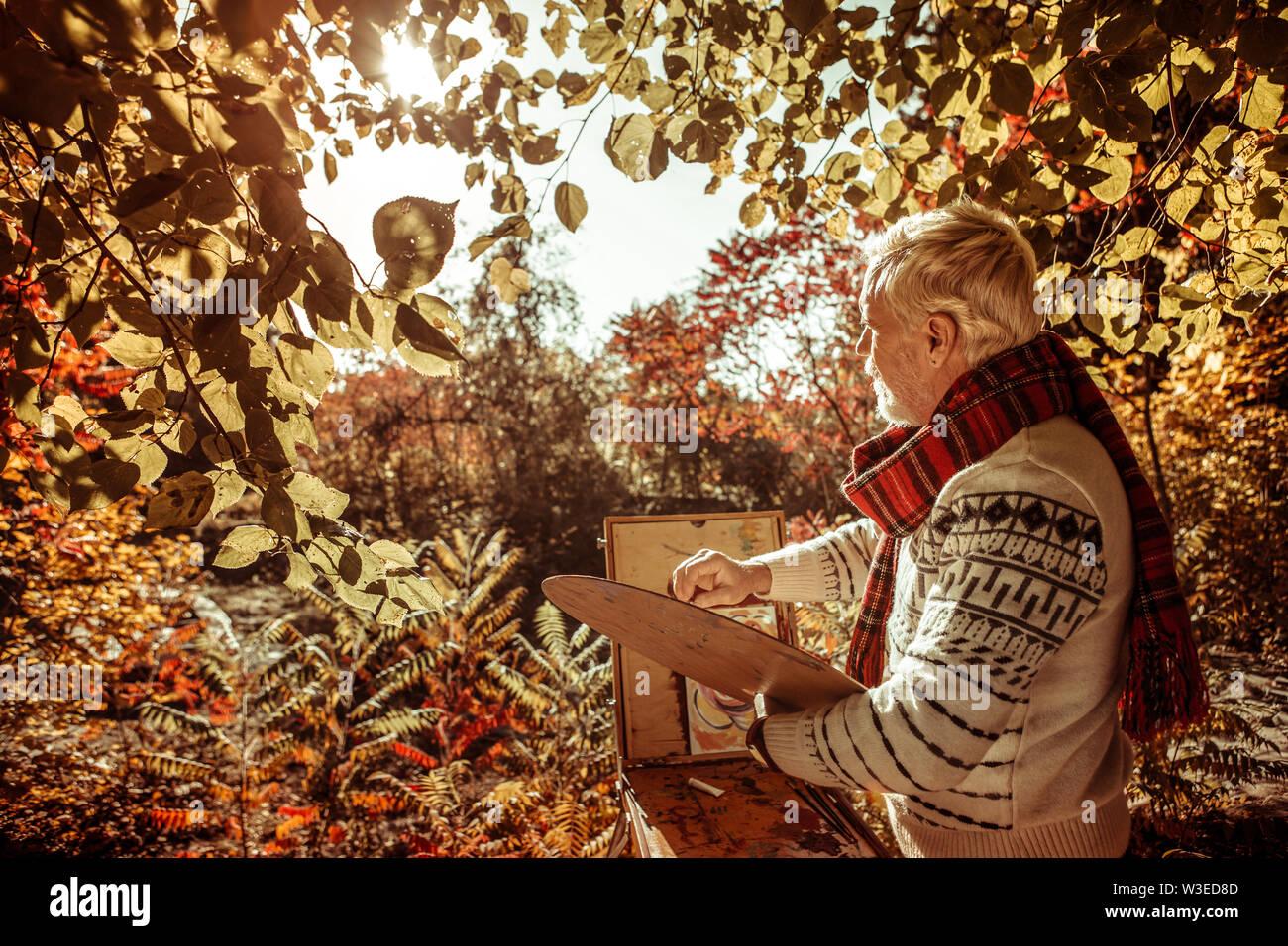Peintre à la recherche réfléchie dans le paysage avant. Photo Stock