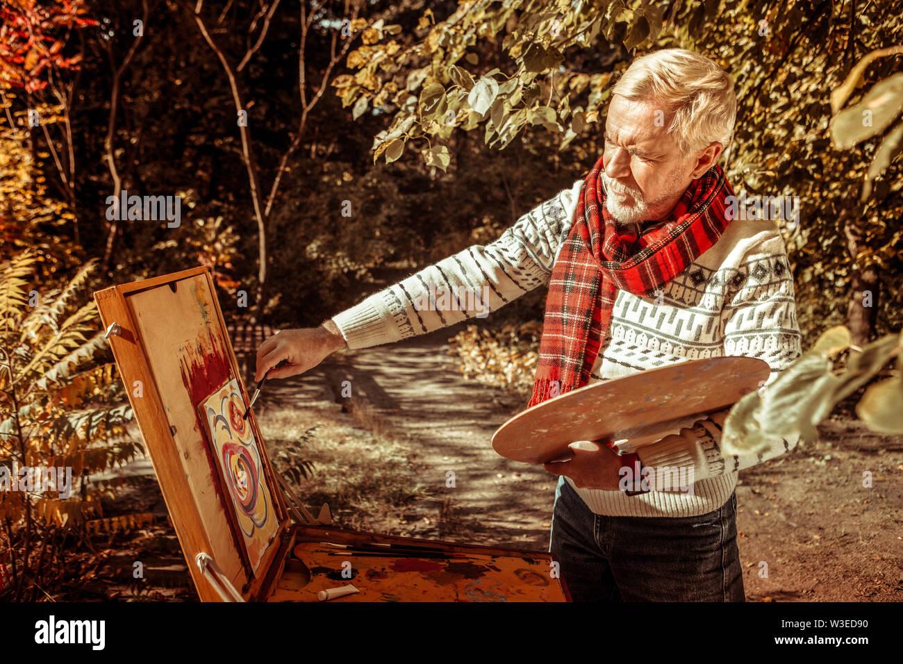 Un homme âgé d'avoir une vue sur le chevalet de dessin. Photo Stock
