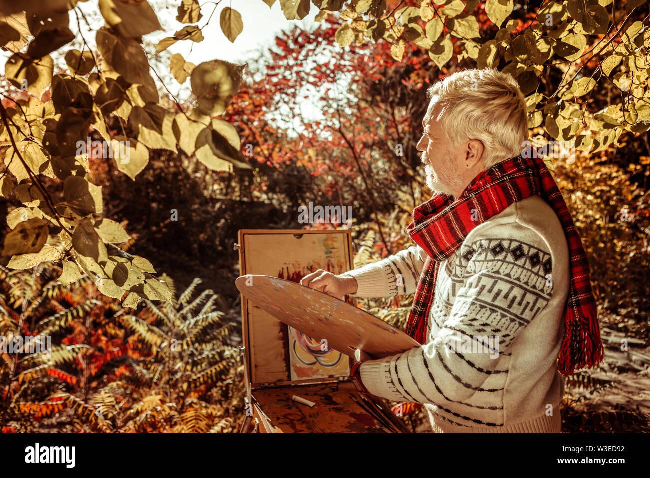 Peintre barbu-gris concentré sur son nouveau travail photo. Photo Stock