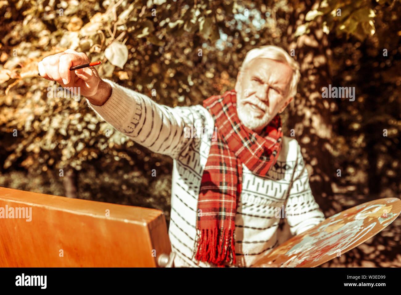 Peintre haute debout devant son chevalet de dessin. Photo Stock