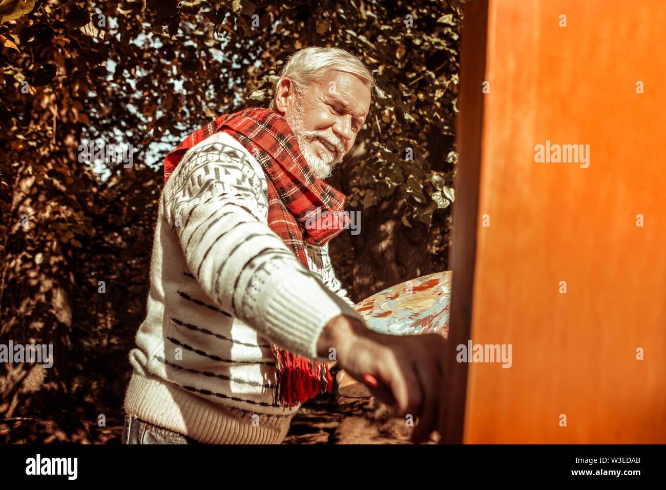 Happy senior man painting une photo dans la nature. Photo Stock