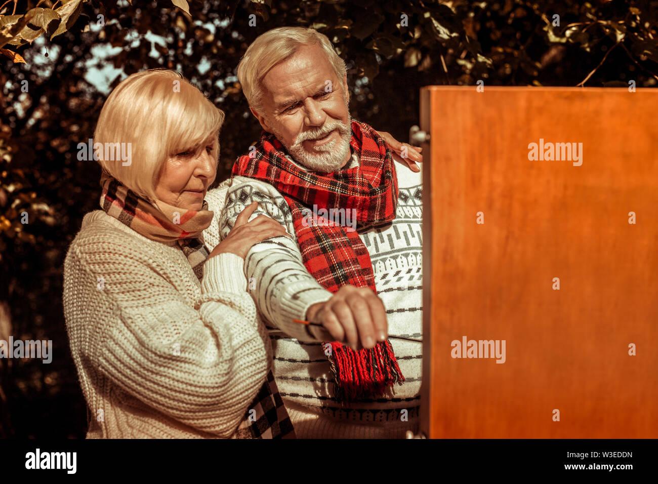 Femme tenant près de son mari la peinture d'une photo. Photo Stock