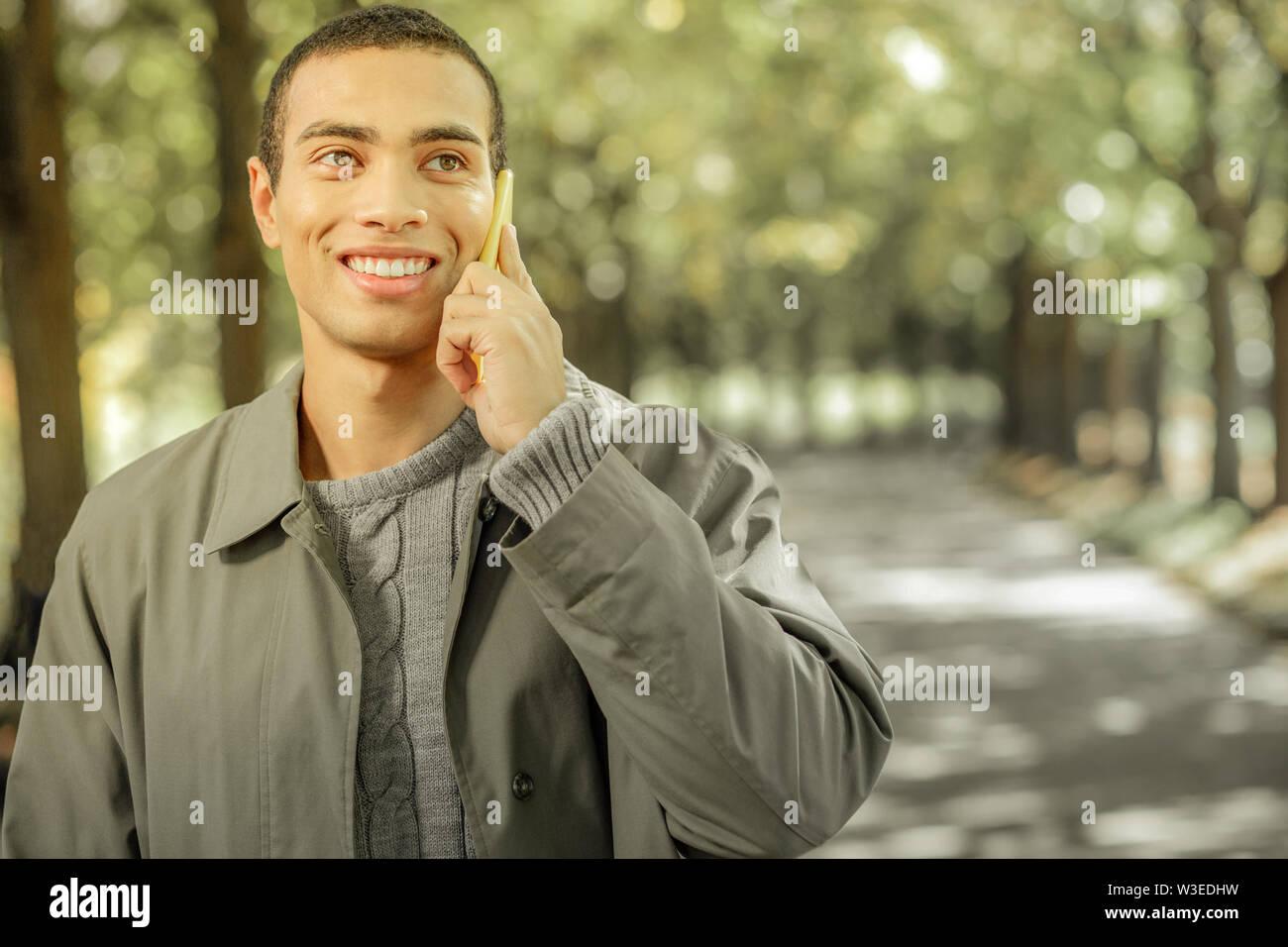 Joyeux beau jeune homme en veston gris avoir conversation Photo Stock