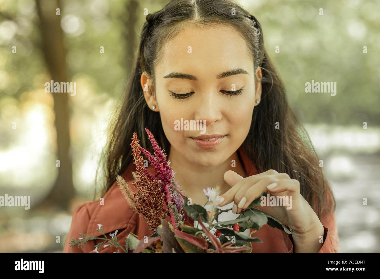 Le plaisir de belles fleurs de printemps d'observation doucement fille Photo Stock