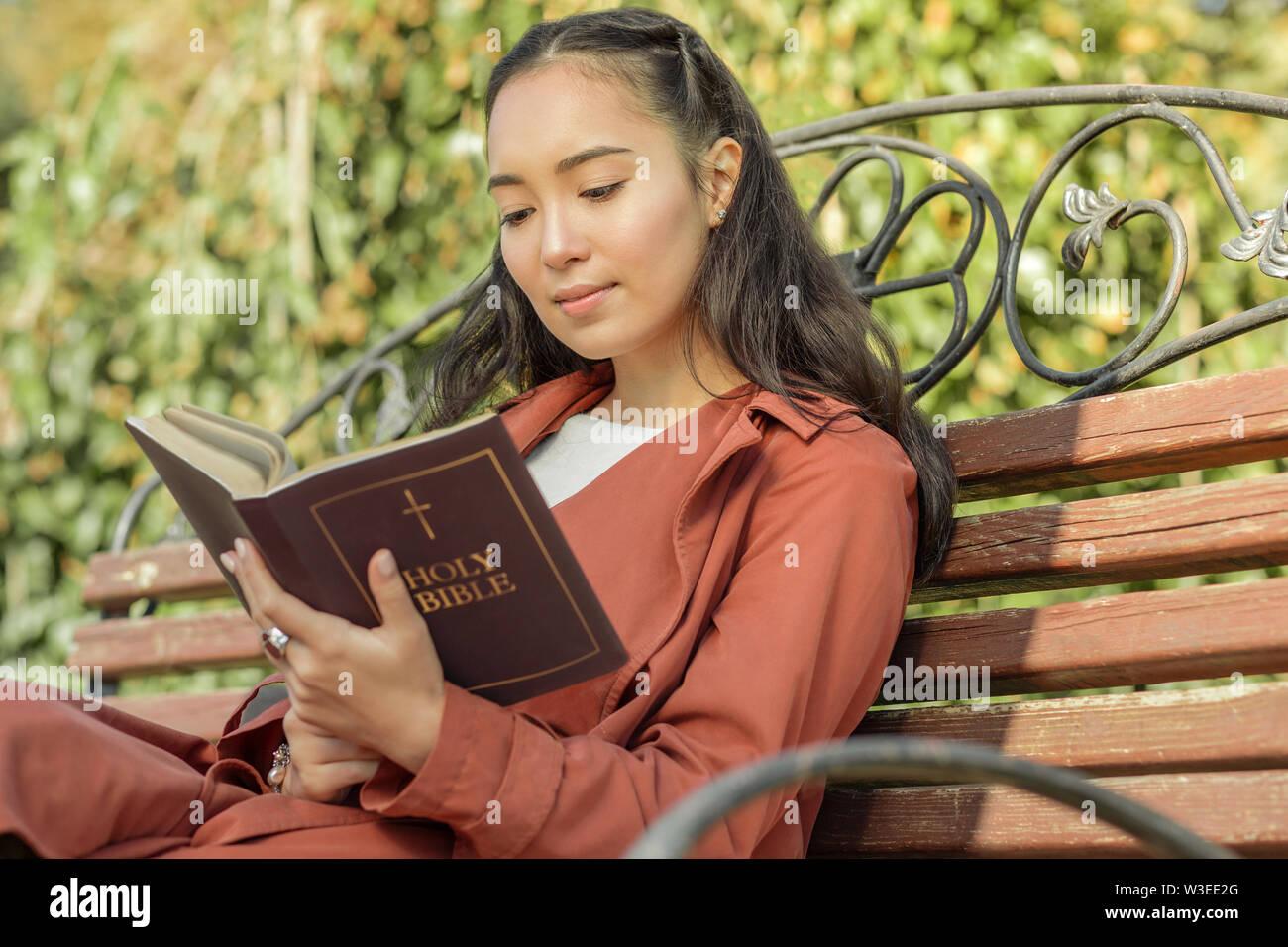 La jeune femme en manteau rouge reposant sur un banc en bois Photo Stock