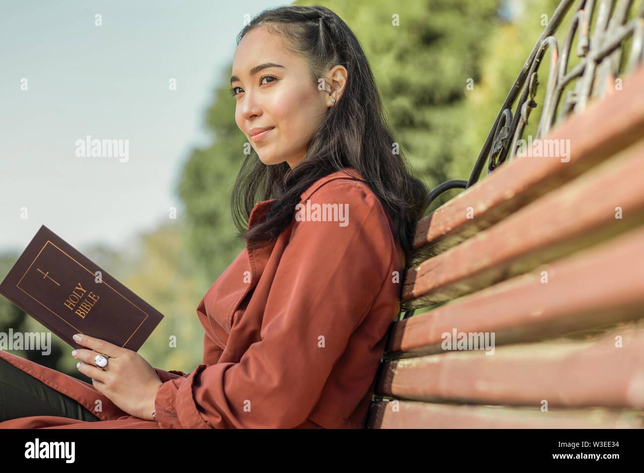 Jeune femme calme avec sourire doux sur une bible Photo Stock