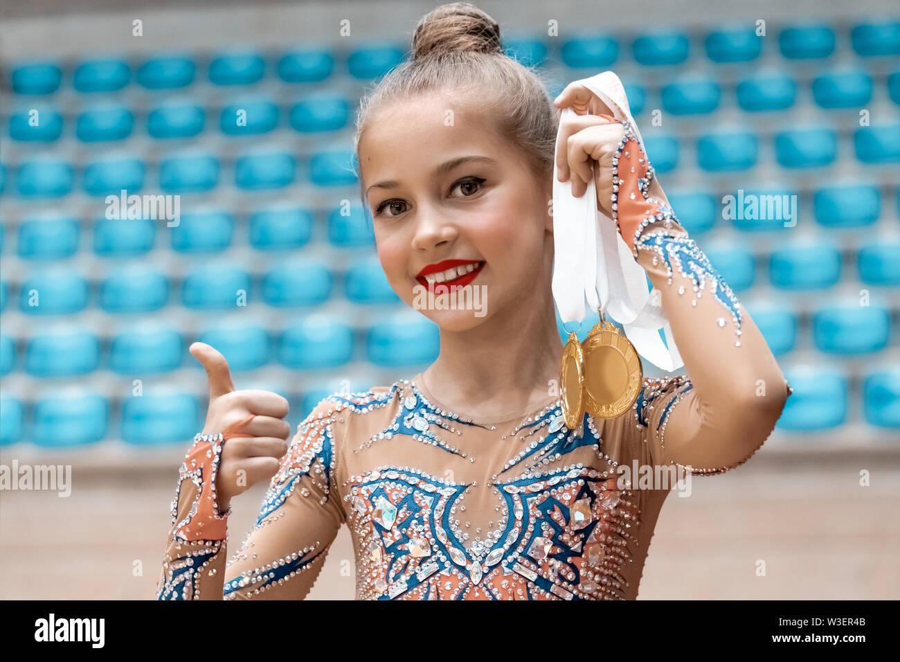 Gagnant du concours de gymnastique rythmique, portrait d'une jolie petite fille tenant en main deux médaille d'or et des gestes par coup de bonne humeur, Photo Stock
