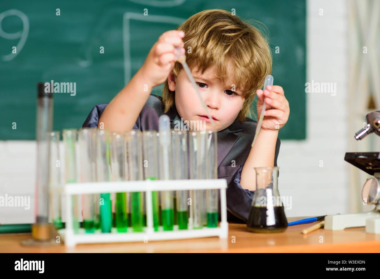 Tubes à essai garçon liquides colorés classe de l'école de chimie. Kid étudier la chimie. Biotechnologies et pharmacie. Élève de Genius. L'analyse chimique. Concept de la science. Wunderkind expérimenter avec la chimie. Photo Stock