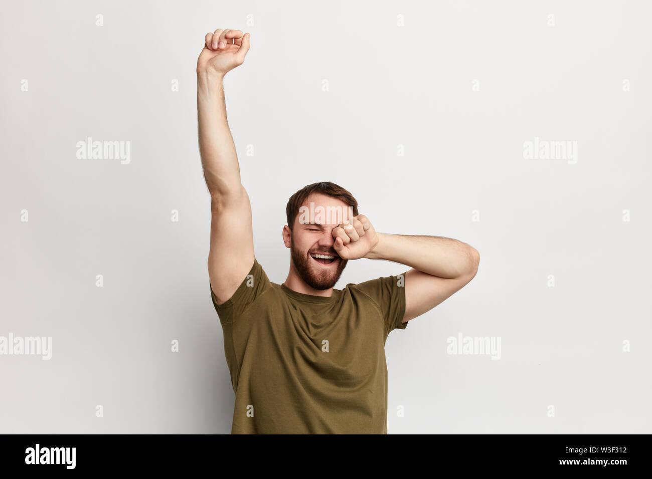 Sleepy man les bâillements et les étirements, isolé sur un fond blanc. lundi, joyeux guy ayant bonne humeur le matin Photo Stock