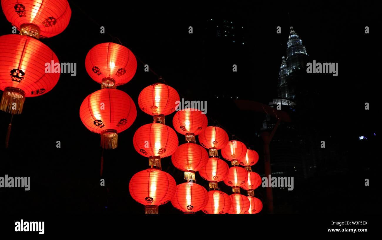 Un gros plan de lanternes en papier dans la nuit avec un haut édifice en arrière-plan Photo Stock