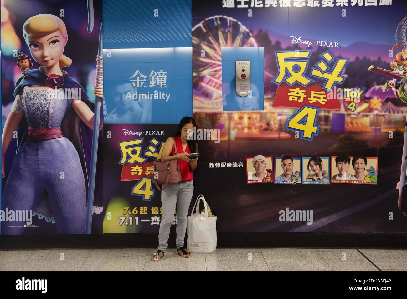 Hong Kong, Chine. 14 juillet, 2019. Un frontalier est à côté d'un grand Pixar Animation Studios' Toy Story 4 film wall publicité à la station de métro de Hong Kong. Budrul Chukrut Crédit: SOPA/Images/ZUMA/Alamy Fil Live News Photo Stock