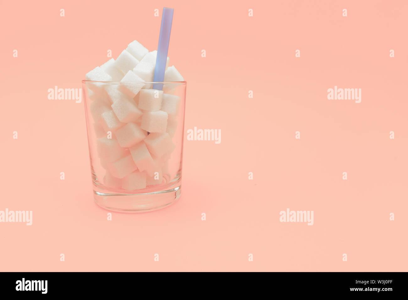 Verre de cubes de sucre avec de la paille sur une belle pêche contexte - mauvaise alimentation concept. Photo Stock