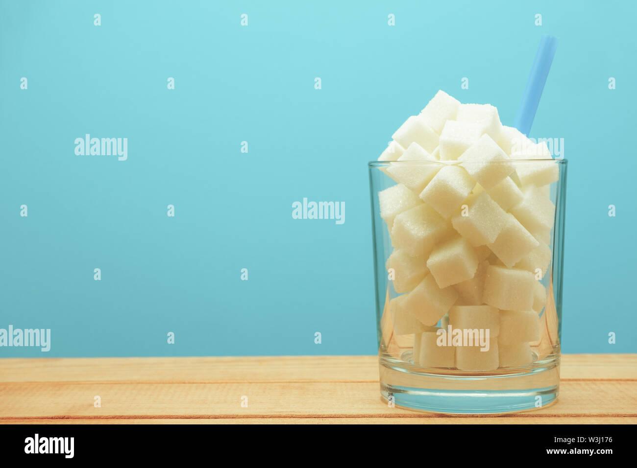 Verre de cubes de sucre avec de la paille sur une table en bois beau fond bleu - mauvaise alimentation concept. Photo Stock
