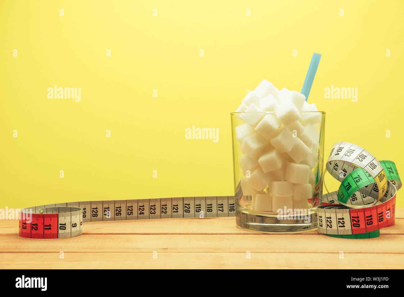 Verre de cubes de sucre avec de la paille sur une table en bois beau fond jaune - mauvaise alimentation concept. Banque D'Images