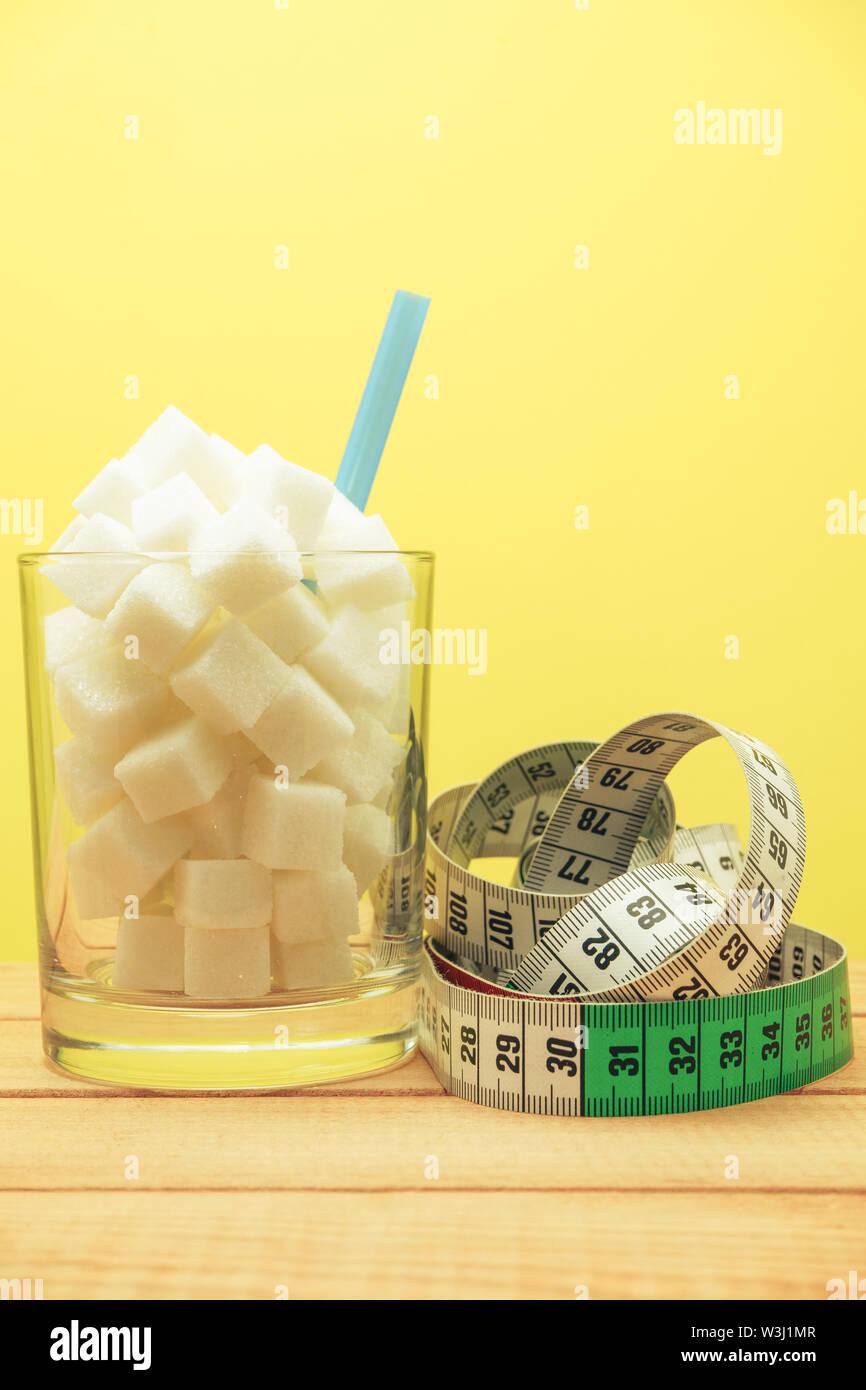 Verre de cubes de sucre avec de la paille sur une table en bois beau fond jaune - mauvaise alimentation concept. Photo Stock