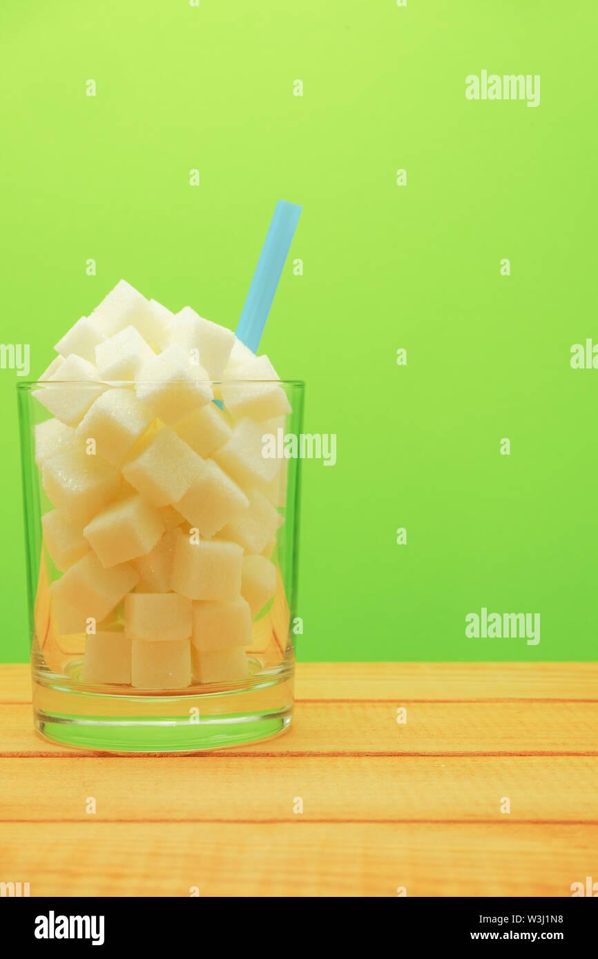 Verre de cubes de sucre avec de la paille sur une table en bois beau fond vert - mauvaise alimentation concept. Photo Stock