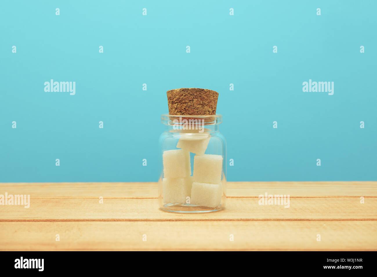 Petit verre bouteille pleine de cubes de sucre sur une table en bois beau fond bleu - mauvaise alimentation concept. Photo Stock