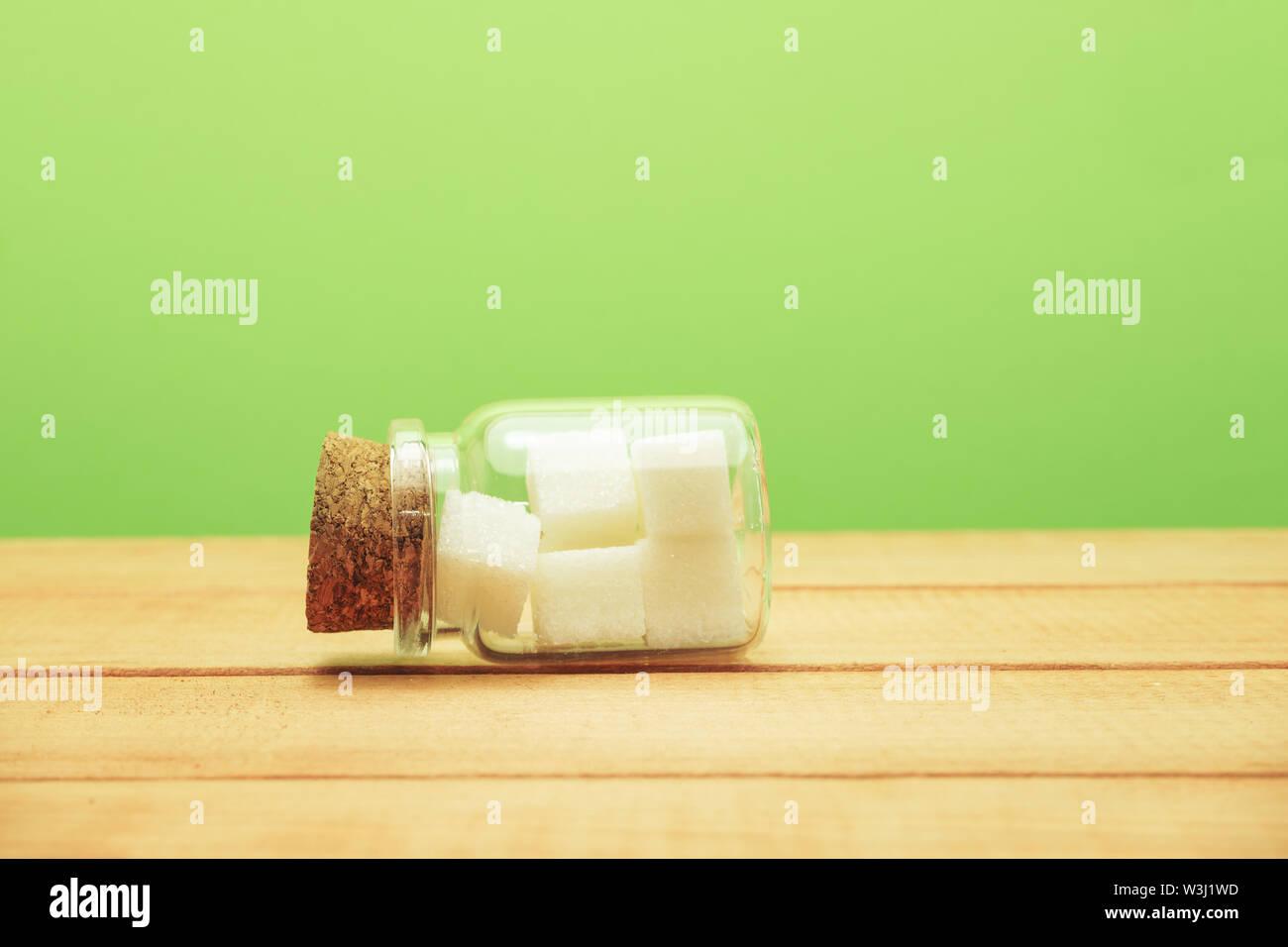 Petit verre bouteille pleine de cubes de sucre sur une table en bois beau fond vert - mauvaise alimentation concept. Photo Stock