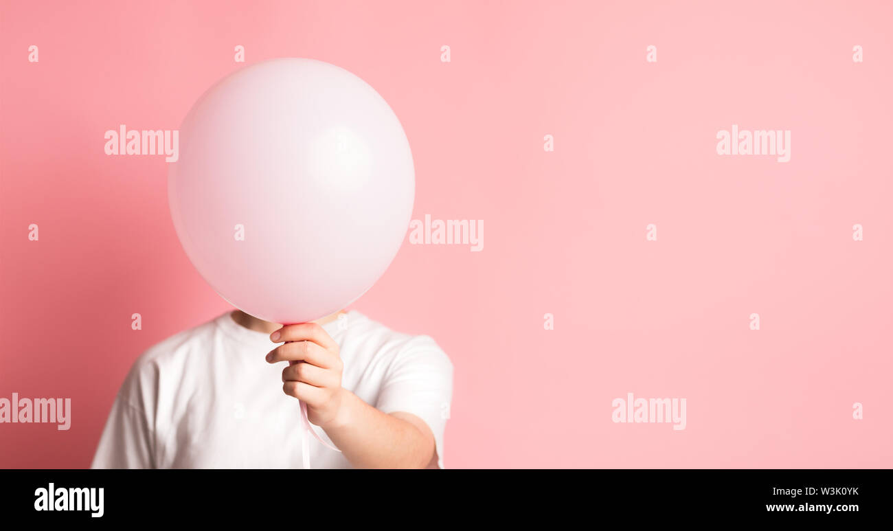 Femme cachant son visage à côté de ballon rose avec l'espace vide Photo Stock