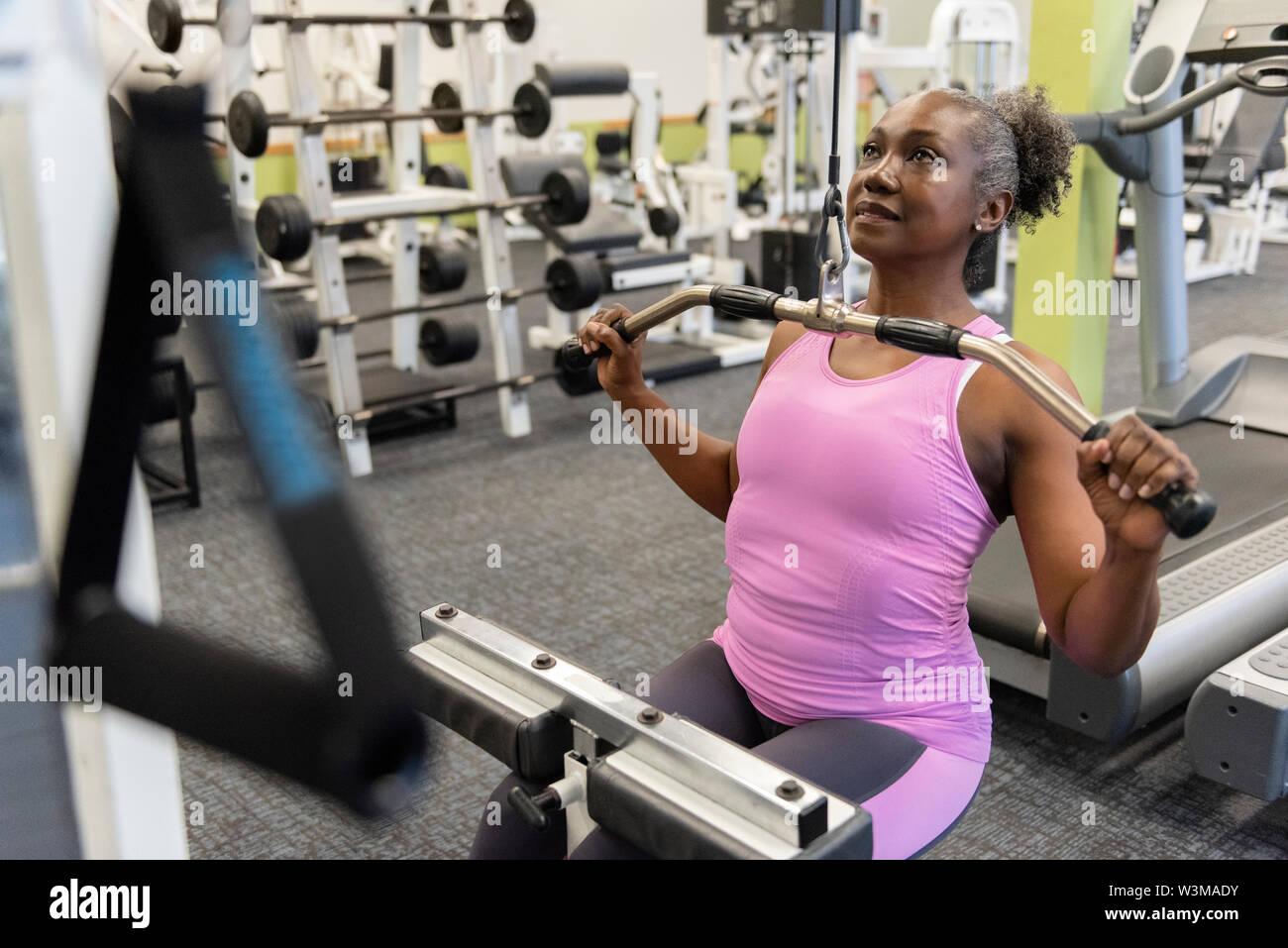 Femme mature la formation de poids dans une salle de sport Banque D'Images