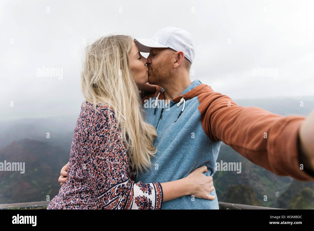 Couple en tenant tout en embrassant selfies Banque D'Images