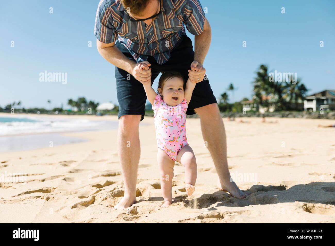 Il aidait son père baby girl walk on beach Banque D'Images