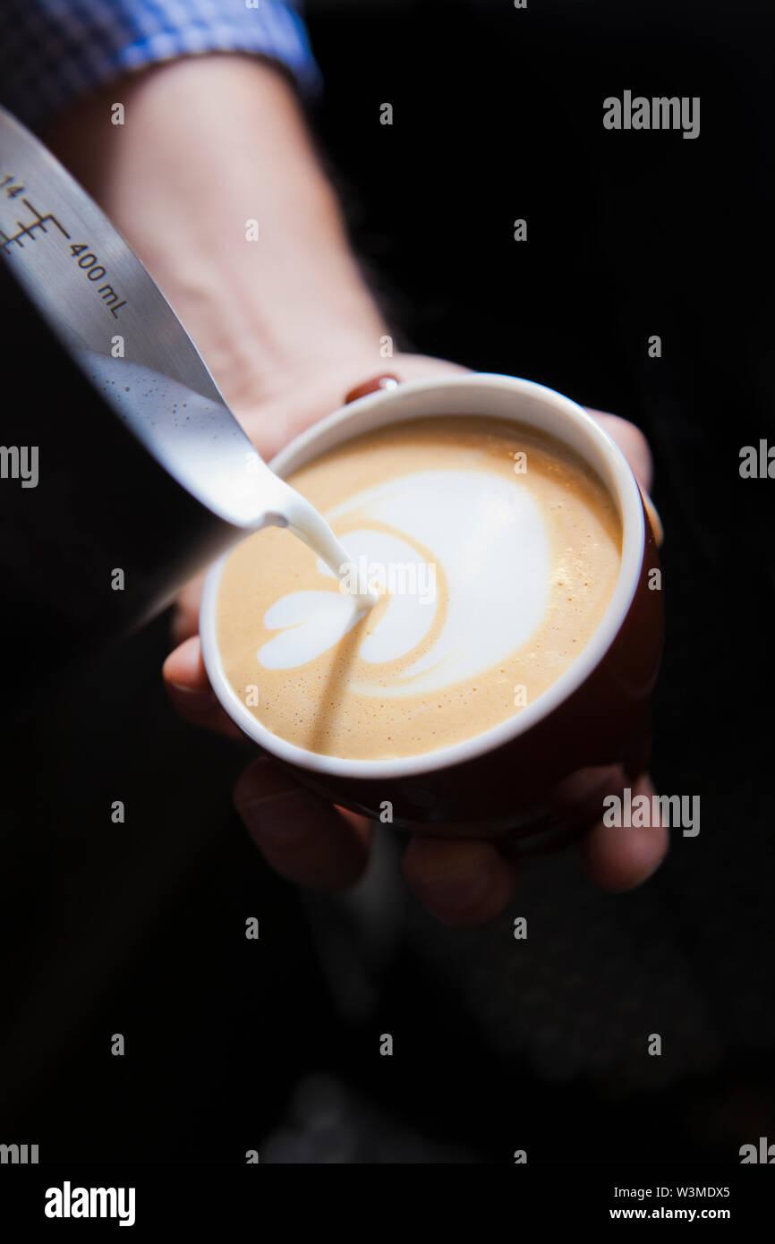 Verser le lait dans le café barista Banque D'Images