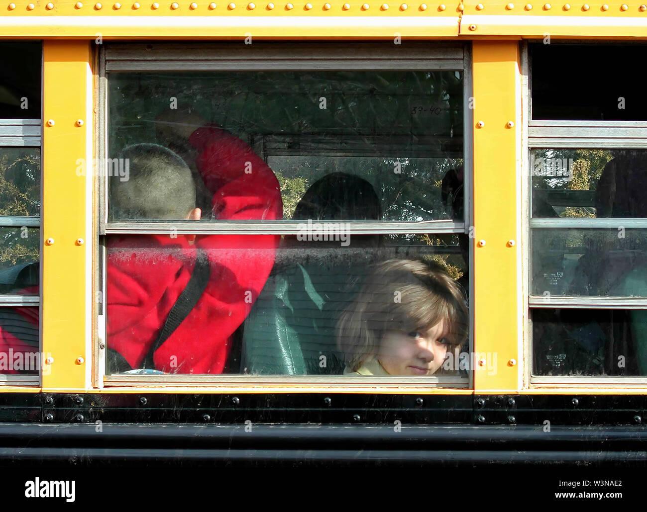 Middletown, CT USA. Mar 2015. Une petite fille à l'intérieur d'un autobus scolaire se détournent de la caméra à un endroit résidentiel drop off. Photo Stock