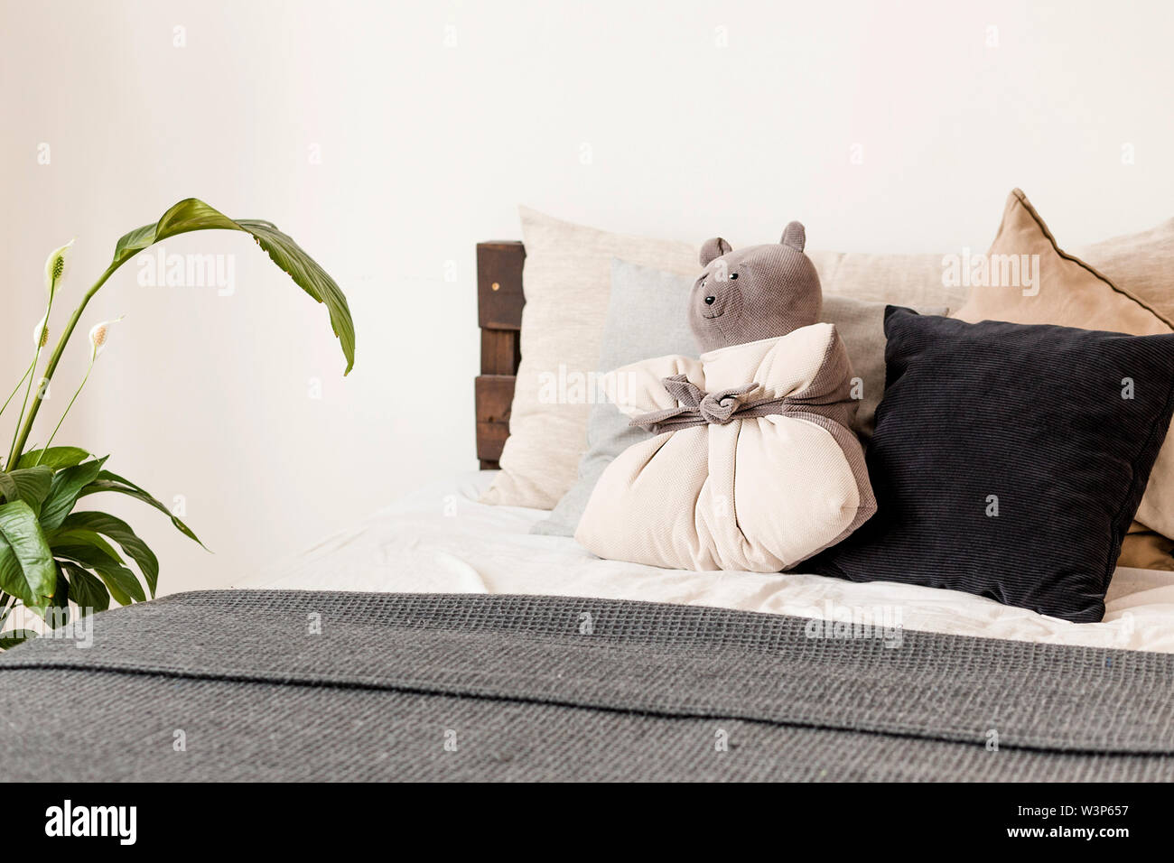 Photo de l'oreiller sous la forme d'un ours couché sur le lit Photo Stock